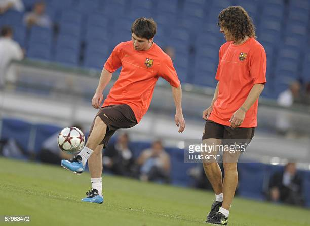 Barcelona's Argentinian midfielder Lionel Messi and captain Carles Puyol take part in a training session at the Olympic stadium in Rome on May 26...