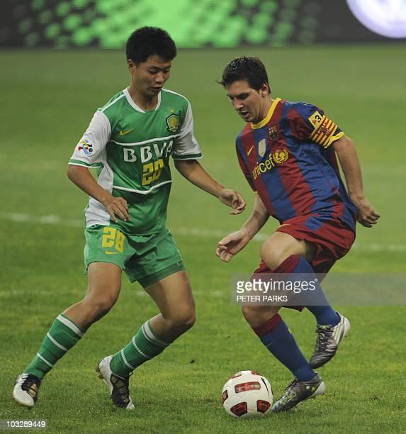 Barcelona's Argentinian midfielder Lionel Messi is challenged by Zhu Yifan of Beijing Guoan in the Bird's Nest Olympic Stadium in Beijing on August 8...
