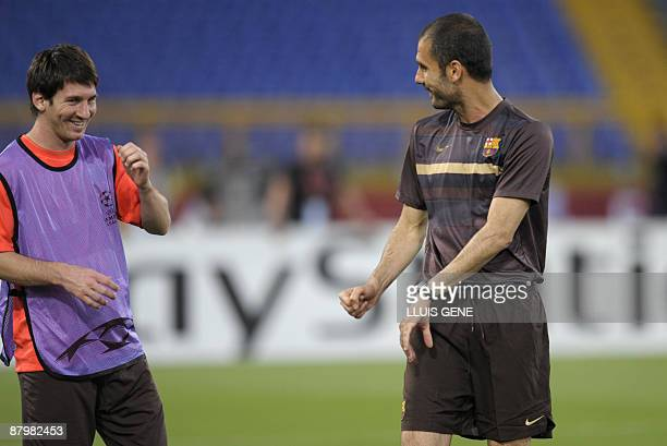 Barcelona's Argentinian midfielder Lionel Messi talks with coach Pep Guardiola during a training session at the Olympic stadium in Rome on May 26...