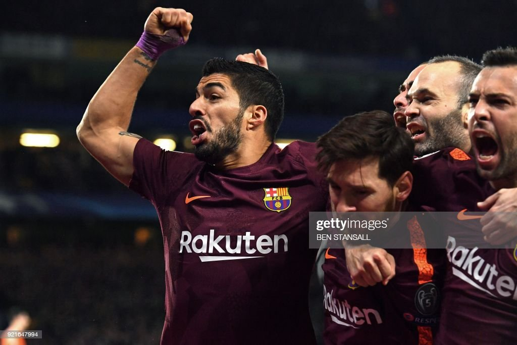 TOPSHOT - Barcelona's Argentinian striker Lionel Messi (C) celebrates with Barcelona's Uruguayan striker Luis Suarez (L) and teammates after scoring their first goal during the first leg of the UEFA Champions League round of 16 football match between Chelsea and Barcelona at Stamford Bridge stadium in London on February 20, 2018. / AFP PHOTO / Ben STANSALL