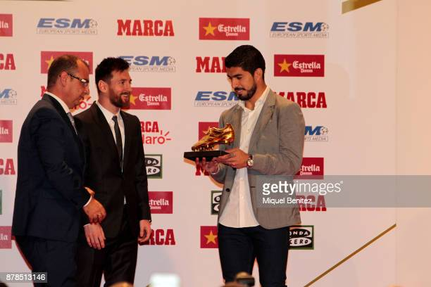 Barcelona's Argentinian striker Lionel Messi receives his fourth Golden Boot Gala trophy from his Uruguayan teammate Luis Suarez as top scorer in all...