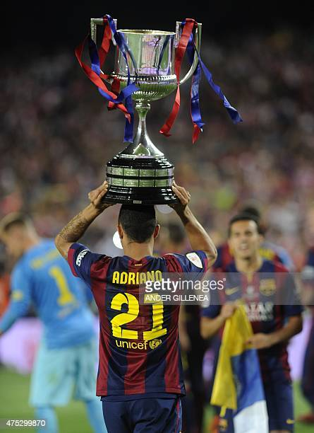 Barcelona's Brazilian defender Adriano celebrates with the trophy after winning the Spanish Copa del Rey final football match Athletic Club Bilbao vs...