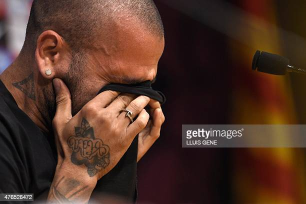 Barcelona's Brazilian defender Dani Alves rubs his eyes during a press conference at Camp Nou stadium in Barcelona on June 10, 2015. Dani Alves put...