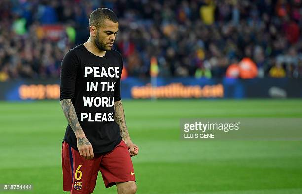 Barcelona's Brazilian defender Dani Alves walks with a jersey that sporting the words 'Peace in the world please' before the Spanish league 'Clasico'...