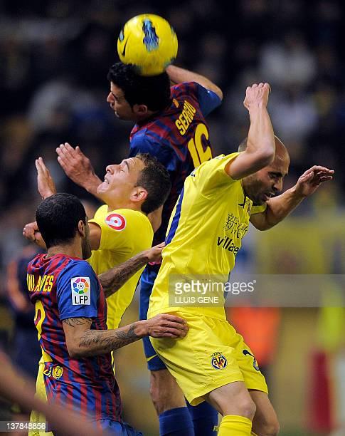 Barcelona's Brazilian defender Daniel Alves and Barcelona's midfielder Sergio Busquets vie with Villarreal's midfielder Cani and Villarreal's...