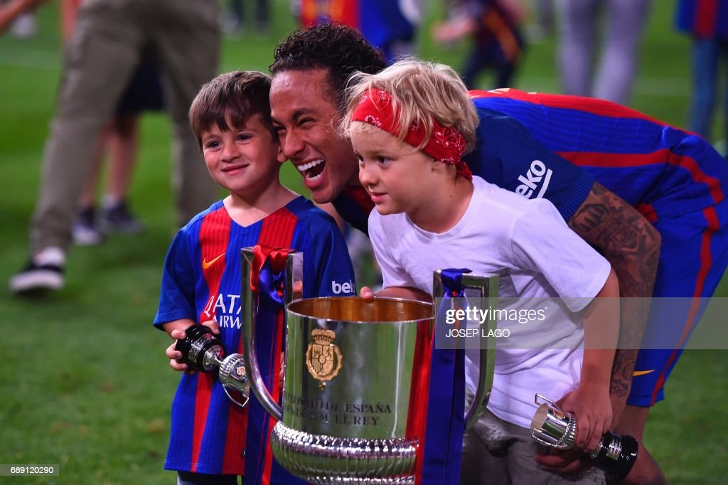 Barcelona's Brazilian forward Neymar (C) and kids pose with the trophy at the end of the Spanish Copa del Rey (King's Cup) final football match FC Barcelona vs Deportivo Alaves at the Vicente Calderon stadium in Madrid on May 27, 2017. Barcelona won 3-1. / AFP PHOTO / Josep LAGO