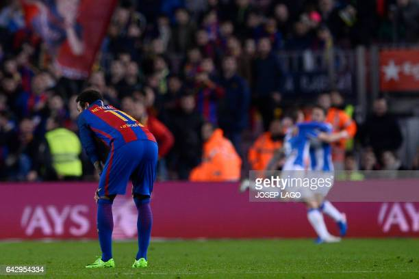 Barcelona's Brazilian forward Neymar bends as Leganes players celebrate a goal during the Spanish league football match FC Barcelona vs CD Leganes at...