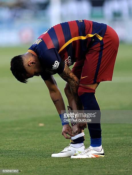 Barcelona's Brazilian forward Neymar bends to adjust his shinguard during the Spanish league football match Real Betis Balompie vs FC Barcelona at...