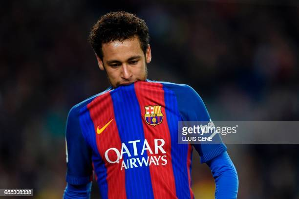 Barcelona's Brazilian forward Neymar bites on his jersey during the Spanish league football match FC Barcelona vs Valencia CF at the Camp Nou stadium...