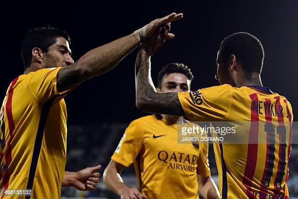 Barcelona's Brazilian forward Neymar celebrates with Barcelona's Uruguayan forward Luis Suarez after scoring a goal during the Spanish league...