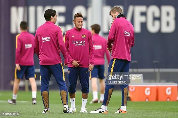 Barcelona's Brazilian forward Neymar chats with Barcelona's Uruguayan forward Luis Suarez and Barcelona's defender Gerard Pique during a training...