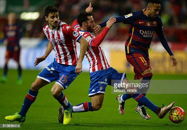 Barcelona's Brazilian forward Neymar controls the ball next to Sporting Gijon's defenders Alex Menendez and Roberto Canella during the Spanish league...