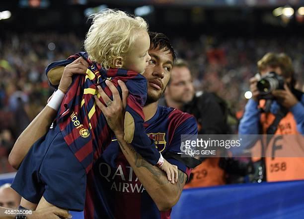 Barcelona's Brazilian forward Neymar da Silva Santos Junior carries his son before the Spanish league football match FC Barcelona vs RC Celta de Vigo...