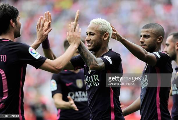 Barcelona's Brazilian forward Neymar da Silva Santos Junior celebrates with teammates after scoring his team's third goal during the Spanish league...