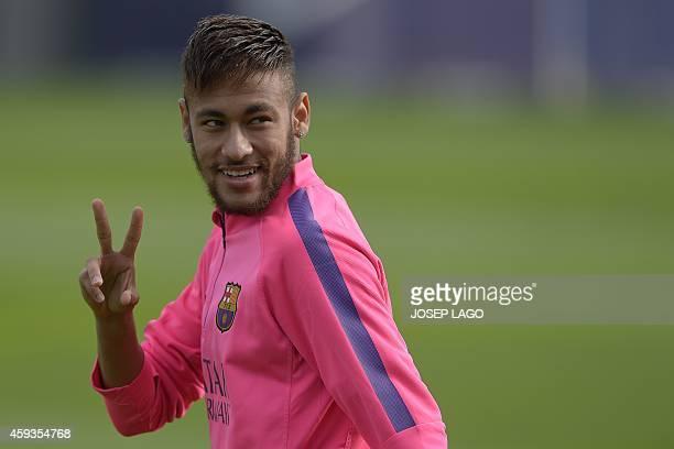 Barcelona's Brazilian forward Neymar da Silva Santos Junior flashes the victory sign during a training session at the Sports Center FC Barcelona Joan...