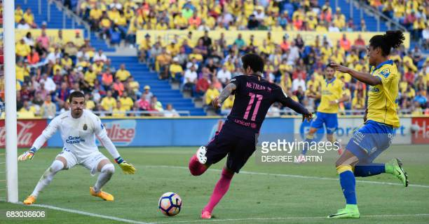 Barcelona's Brazilian forward Neymar da Silva Santos Junior kicks the ball between Las Palmas' Uruguayan defender Mauricio Lemos and Las Palmas'...