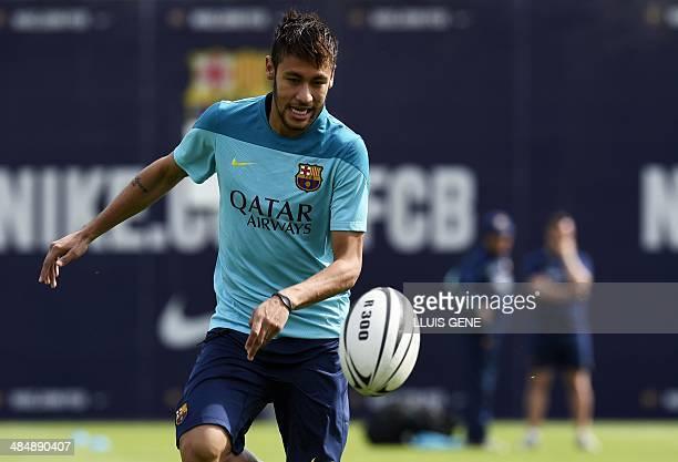 Barcelona's Brazilian forward Neymar da Silva Santos Junior plays with a rugby ball during a training session at the Sports Center FC Barcelona Joan...