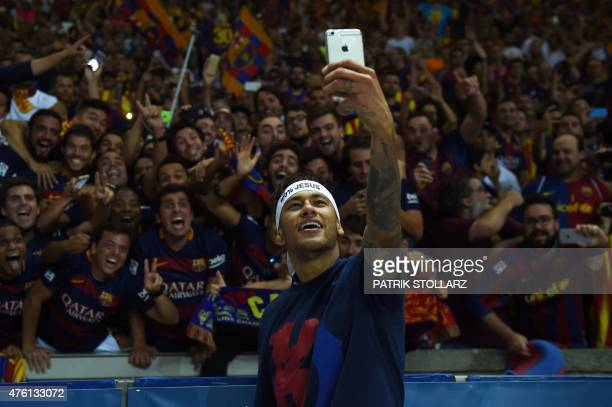 Barcelona's Brazilian forward Neymar da Silva Santos Junior takes selfies with fans after the UEFA Champions League Final football match between...