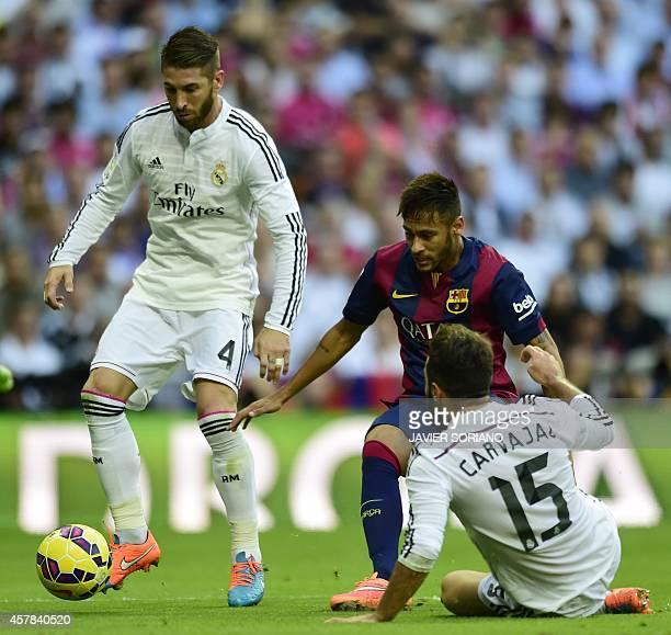 Barcelona's Brazilian forward Neymar da Silva Santos Junior vies with Real Madrid's defender Dani Carvajal and Real Madrid's defender Sergio Ramos...