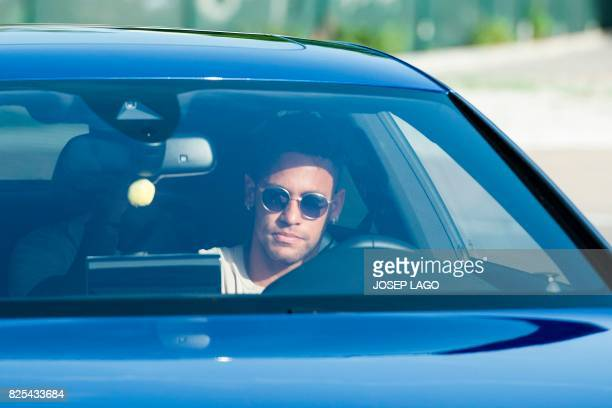 TOPSHOT Barcelona's Brazilian forward Neymar drives into the parkinglot to takes part in a training session at the Sports Center FC Barcelona Joan...