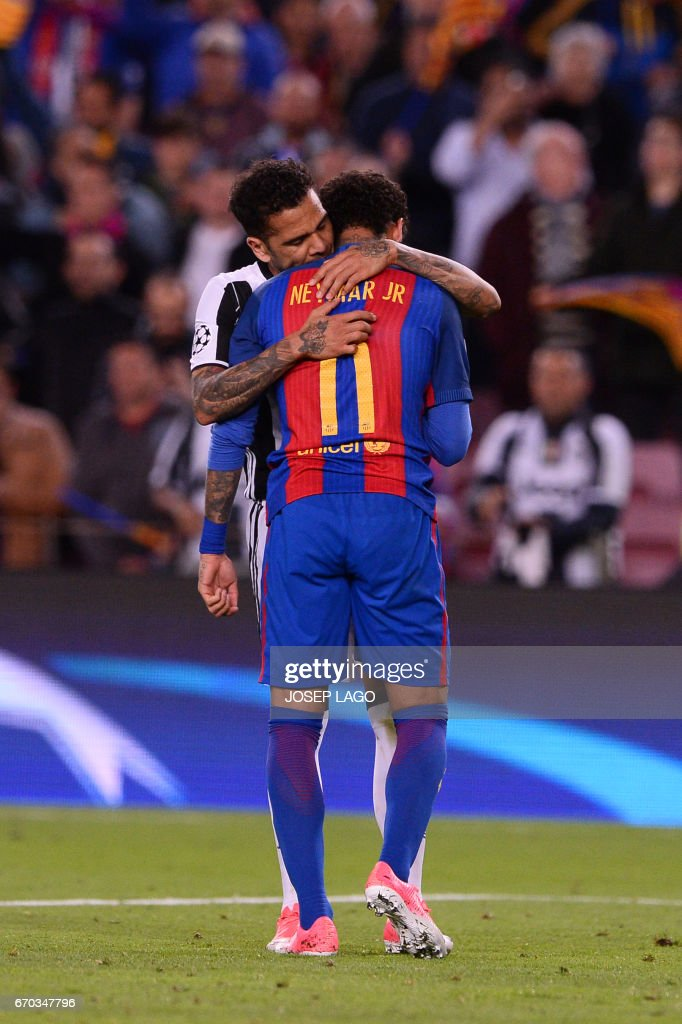 TOPSHOT - Barcelona's Brazilian forward Neymar (R) is comforted by Juventus' Brazilian defender Dani Alves after their disqualification by Juventus at the end of the UEFA Champions League quarter-final second leg football match FC Barcelona vs Juventus at the Camp Nou stadium in Barcelona on April 19, 2017. The game ended with a draw and Juventus is qualified for the semis. / AFP PHOTO / Josep LAGO