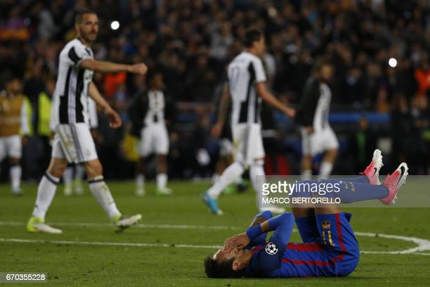 TOPSHOT Barcelona's Brazilian forward Neymar lies on the field on the field during the UEFA Champions League quarterfinal second leg football match...