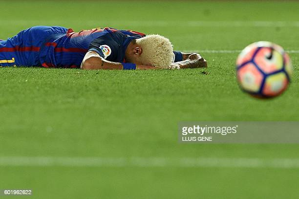 Barcelona's Brazilian forward Neymar lies on the pitch after missing a goal during the Spanish league football match FC Barcelona vs Deportivo Alaves...