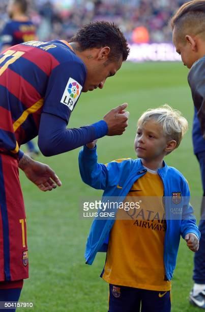 Barcelona's Brazilian forward Neymar slaps hands with his son before the Spanish league football match FC Barcelona vs Granada CF at the Camp Nou...