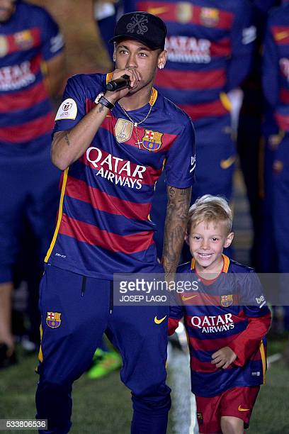 Barcelona's Brazilian forward Neymar speaks next to his son David Lucca during celebrations at the Camp Nou stadium in Barcelona on May 23, 2016...