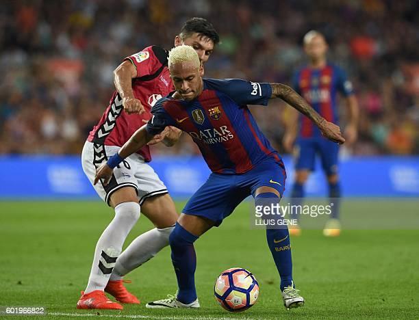 Barcelona's Brazilian forward Neymar vies with Alaves' Colombian midfielder Daniel Torres during the Spanish league football match FC Barcelona vs...