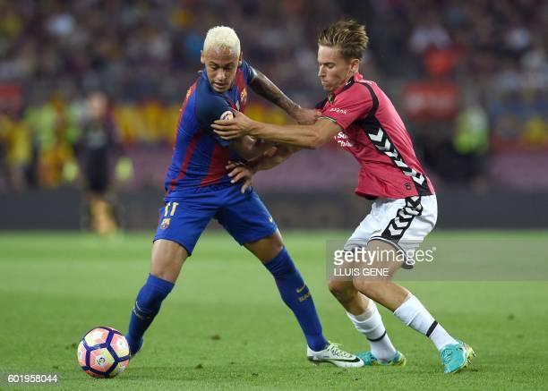 Barcelona's Brazilian forward Neymar vies with Alaves' defender Raul Garcia during the Spanish league football match FC Barcelona vs Deportivo Alaves...