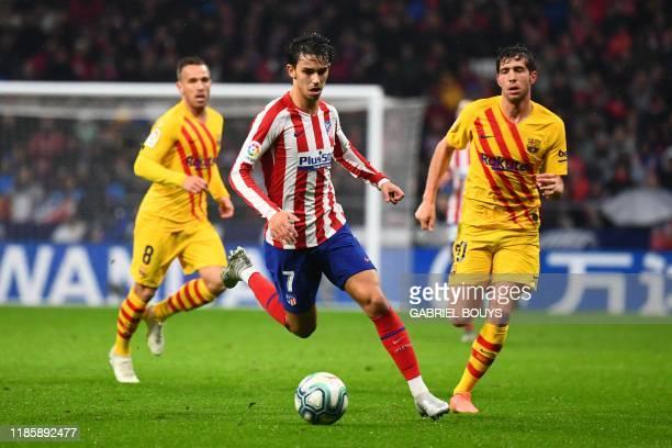 Barcelona's Brazilian midfielder Arthur and Barcelona's Spanish defender Sergi Roberto challenge Atletico Madrid's Portuguese forward Joao Felix...