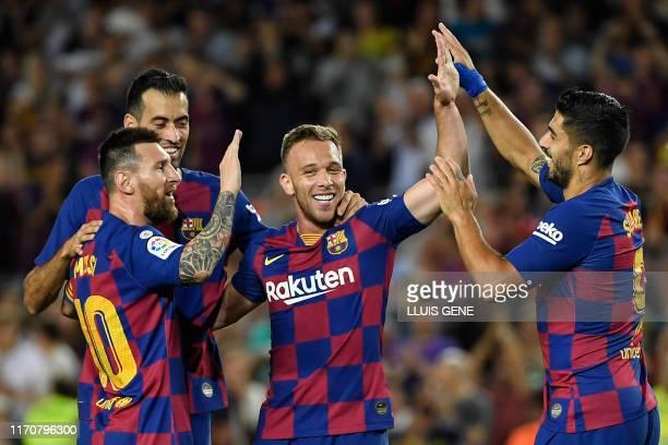 Barcelona's Brazilian midfielder Arthur is congratulated by teammates Barcelona's Argentine forward Lionel Messi and Barcelona's Uruguayan forward...