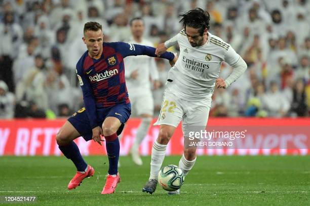 Barcelona's Brazilian midfielder Arthur vies with Real Madrid's Spanish midfielder Isco during the Spanish League football match between Real Madrid...