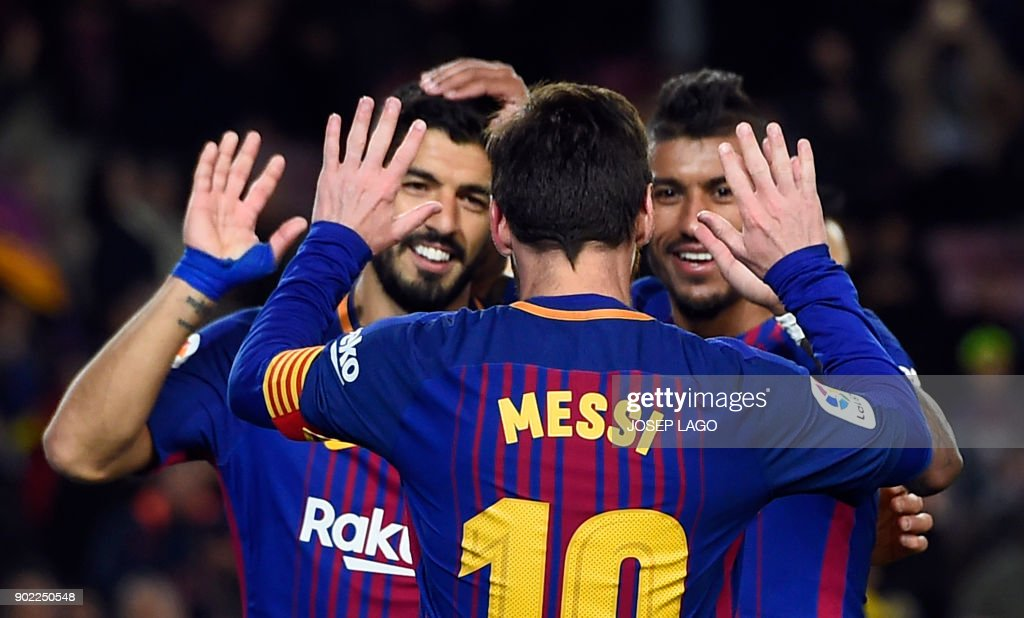 TOPSHOT - Barcelona's Brazilian midfielder Paulinho (R) celebrates a goal with Barcelona's Argentinian forward Lionel Messi and Barcelona's Uruguayan forward Luis Suarez (L) during the Spanish league football match FC Barcelona vs Levante UD at the Camp Nou stadium in Barcelona on January 7, 2018. / AFP PHOTO / Josep LAGO