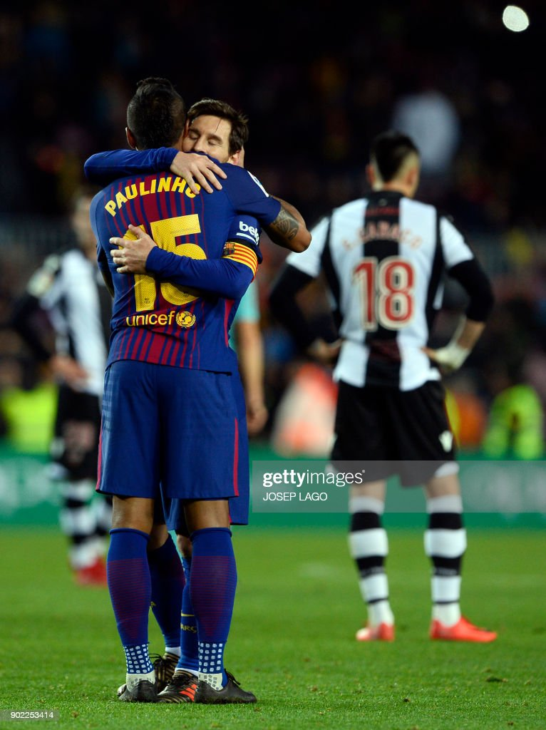Barcelona's Brazilian midfielder Paulinho (L) celebrates a goal with Barcelona's Argentinian forward Lionel Messi during the Spanish league football match FC Barcelona vs Levante UD at the Camp Nou stadium in Barcelona on January 7, 2018. / AFP PHOTO / Josep LAGO