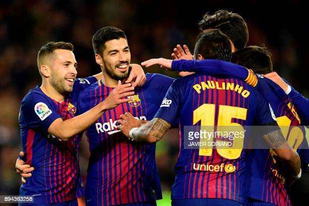 TOPSHOT Barcelona's Brazilian midfielder Paulinho celebrates with Barcelona's Uruguayan forward Luis Suarez Barcelona's Spanish defender Jordi Alba...