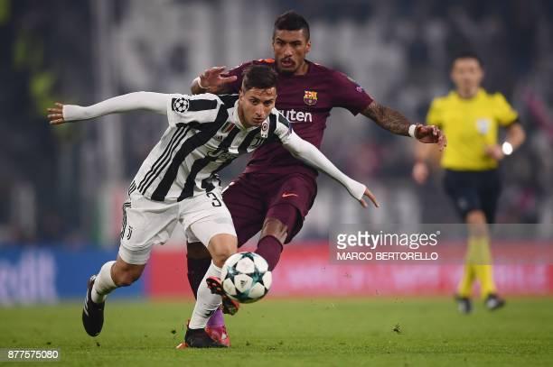 Barcelona's Brazilian midfielder Paulinho fights for the ball with Juventus' midfielder from Uruguay Rodrigo Bentancur during the UEFA Champions...