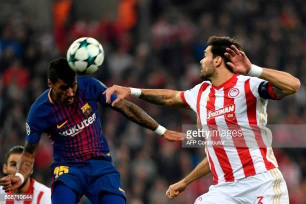 Barcelona's Brazilian midfielder Paulinho heads the ball next to Olympiakos' Spanish defender Alberto Botia during the UEFA Champions League group D...