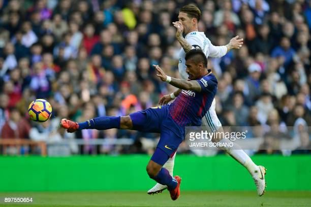 Barcelona's Brazilian midfielder Paulinho kicks the ball next to Real Madrid's Spanish defender Sergio Ramos during the Spanish League 'Clasico'...