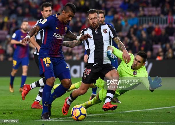 Barcelona's Brazilian midfielder Paulinho vies with Levante's Spanish goalkeeper Oier Olazabal and Levante's Spanish defender Antonio Luna during the...