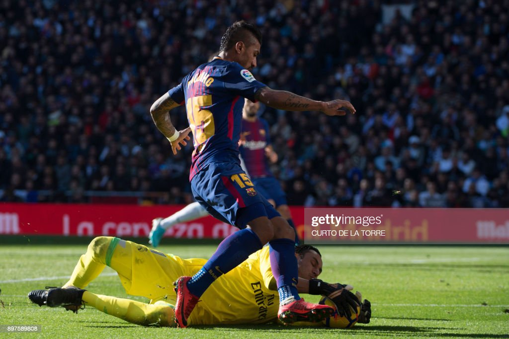 Barcelona's Brazilian midfielder Paulinho (up) vies with Real Madrid's Costa Rican goalkeeper Keylor Navas during the Spanish League 'Clasico' football match Real Madrid CF vs FC Barcelona at the Santiago Bernabeu stadium in Madrid on December 23, 2017. /