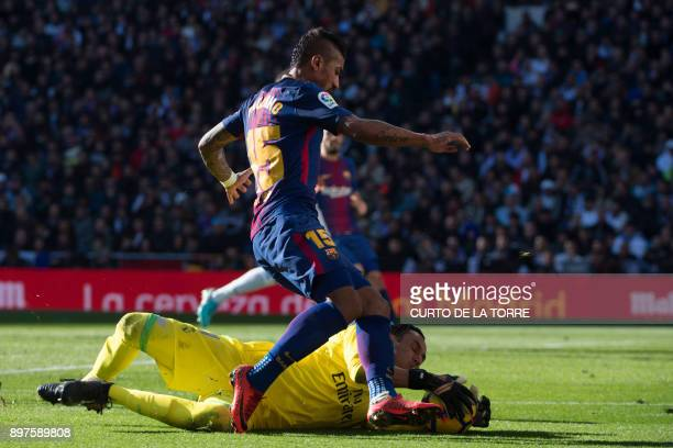 Barcelona's Brazilian midfielder Paulinho vies with Real Madrid's Costa Rican goalkeeper Keylor Navas during the Spanish League 'Clasico' football...