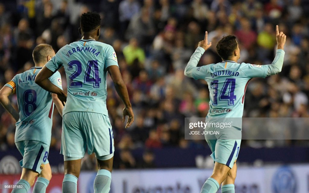 Barcelona's Brazilian midfielder Philippe Coutinho (R) celebrates after scoring a goal during the Spanish league football match between Levante and Barcelona at the Ciutat de Valencia stadium in Valencia on May 13, 2018.