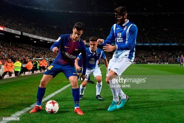 Barcelona's Brazilian midfielder Philippe Coutinho challenges Espanyol's Spanish midfielder David Lopez and Espanyol's Spanish midfielder Oscar...