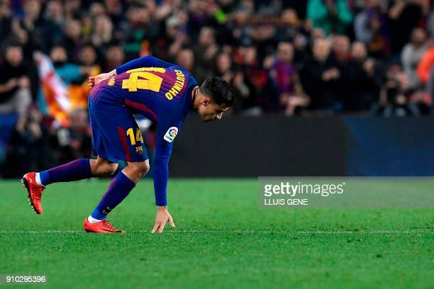 Barcelona's Brazilian midfielder Philippe Coutinho touches the ground as he enters the game during the Spanish 'Copa del Rey' quarterfinal second leg...