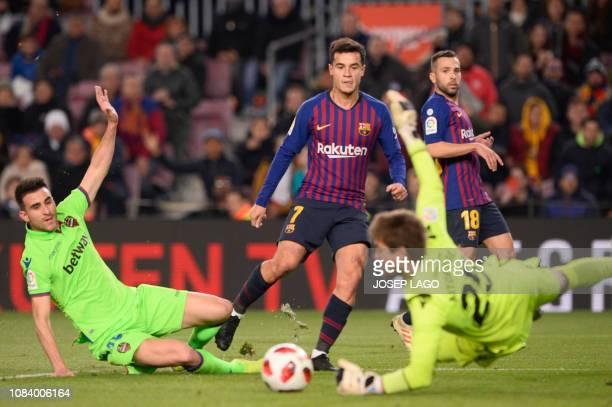 Barcelona's Brazilian midfielder Philippe Coutinho vies with Levante's Spanish goalkeeper Aitor Fernandez and Levante's Spanish defender Sergio...