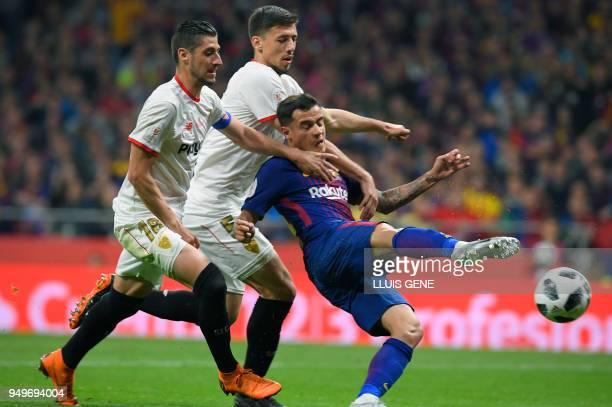 Barcelona's Brazilian midfielder Philippe Coutinho vies with Sevilla's Spanish defender Sergio Escudero and Sevilla's French defender Clement Lenglet...
