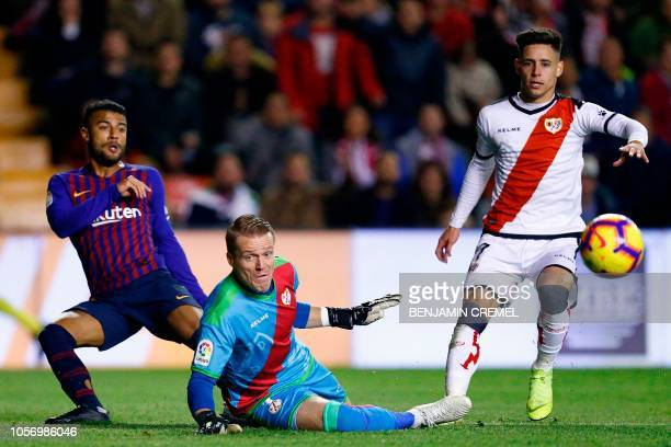 Barcelona's Brazilian midfielder Rafinha reacts as Rayo Vallecano's Spanish goalkeeper Alberto Garcia blocks his shot on goal next to Rayo...