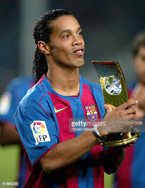 Barcelona's Brazilian midfielder Ronaldinho dedicates to the audience his best 'FIFA 2004' player of the year trophy during a Spanish League soccer...